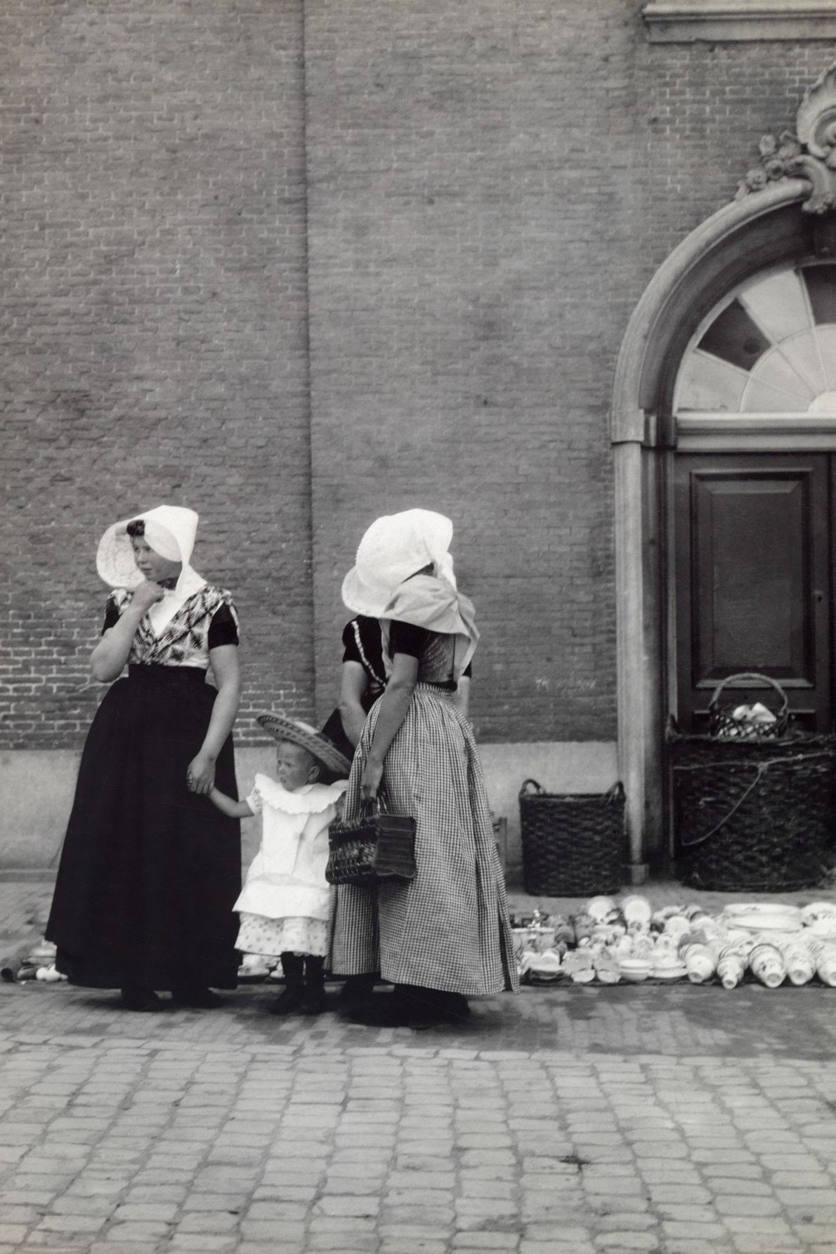 A maid and her mistress hold the hands of a small child while shopping for dishes ...