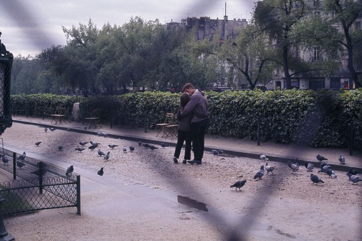 Beside Notre Dame, a strolling couple steal a kiss in a rain-washed garden, once the site ...