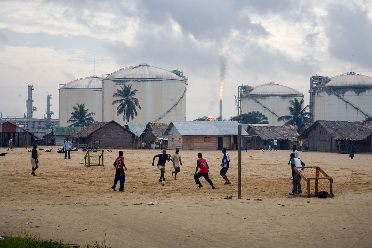 Young men play football in front of gas storage tanks in Bonny Island, Nigeria.