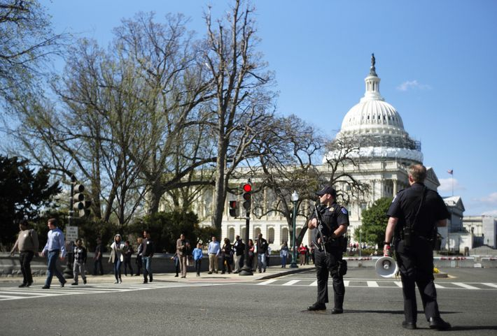 U.S. Capitol Police stand guard in the middle of Independence Avenue as people evacuate the Capitol ...