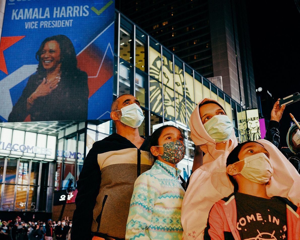 Ali, from Pakistan, celebrates the win of the Biden-Harris campaign with his family in Times Square. ...