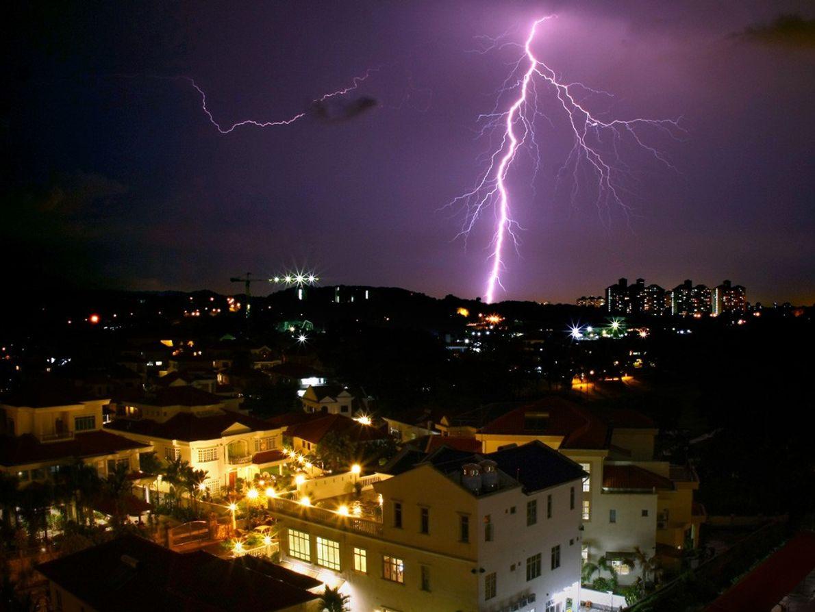 Lightning illuminates the horizon behind a Malaysian cityscape.