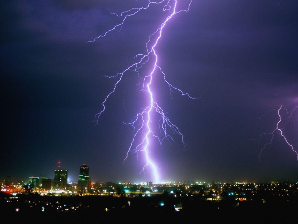 The Tucson, Arizona, skyline is  illuminated by a bolt of lightning.