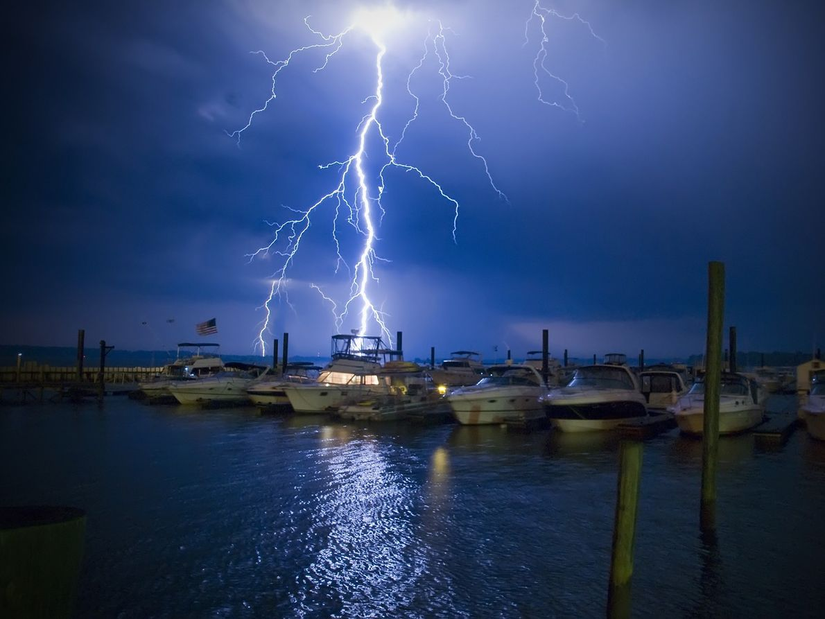 The inhabitants of a powerboat turn on their lights just as a bolt of  lightning ...