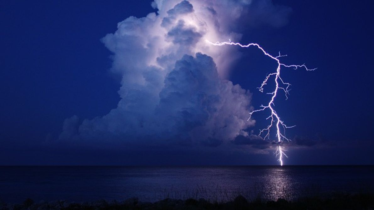 Lightning arcs from the top of a cloud to the horizon off the coast of the ...