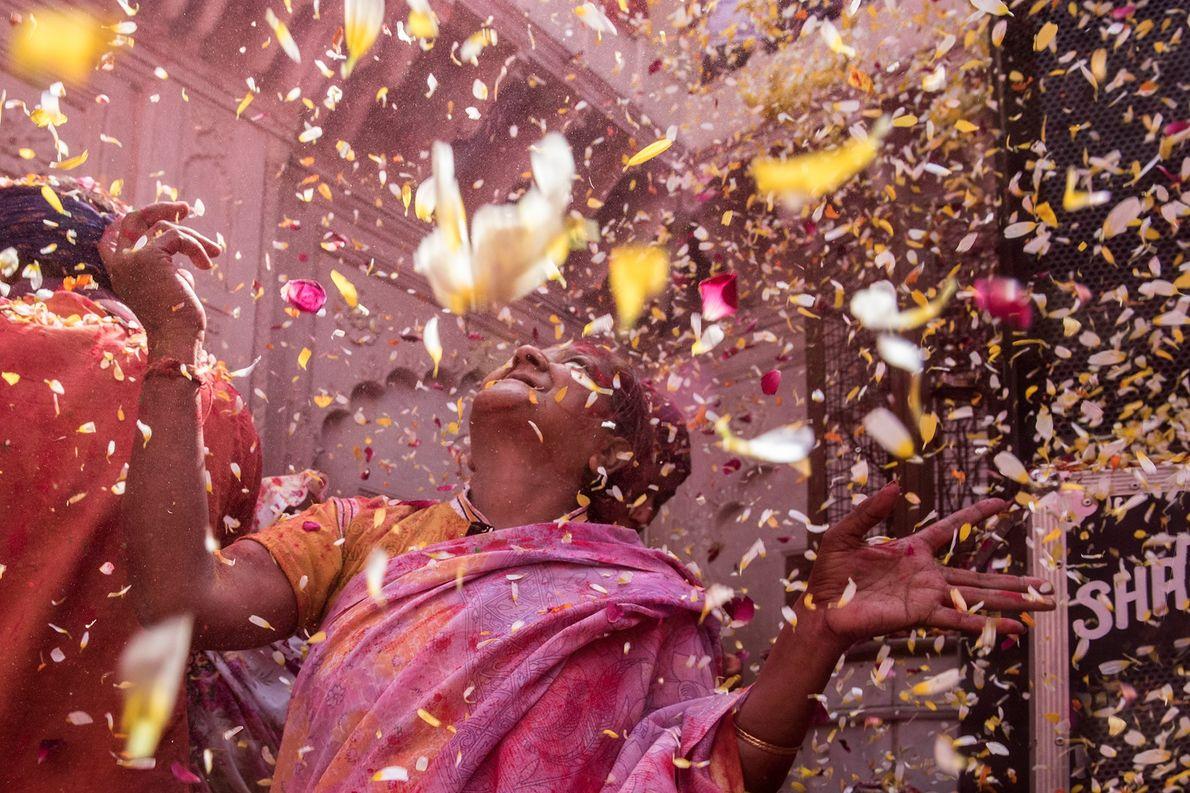 An elderly widow joyfully celebrates Holi by showering petals at the Gopinath Temple, Vrindaban.