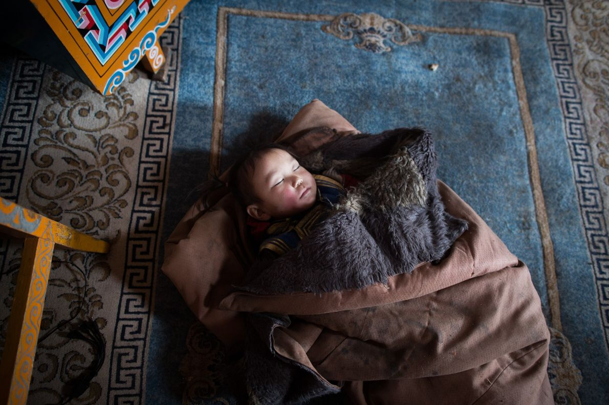A child sleeps in his family's yurt.