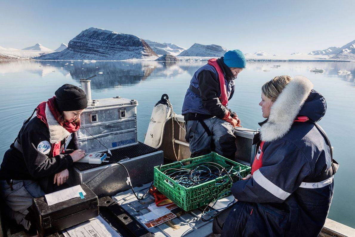 German biologists Clara Hoppe (centre), Klara Wolf (left), and Laura Wischnewski (right) take underwater measurements at ...