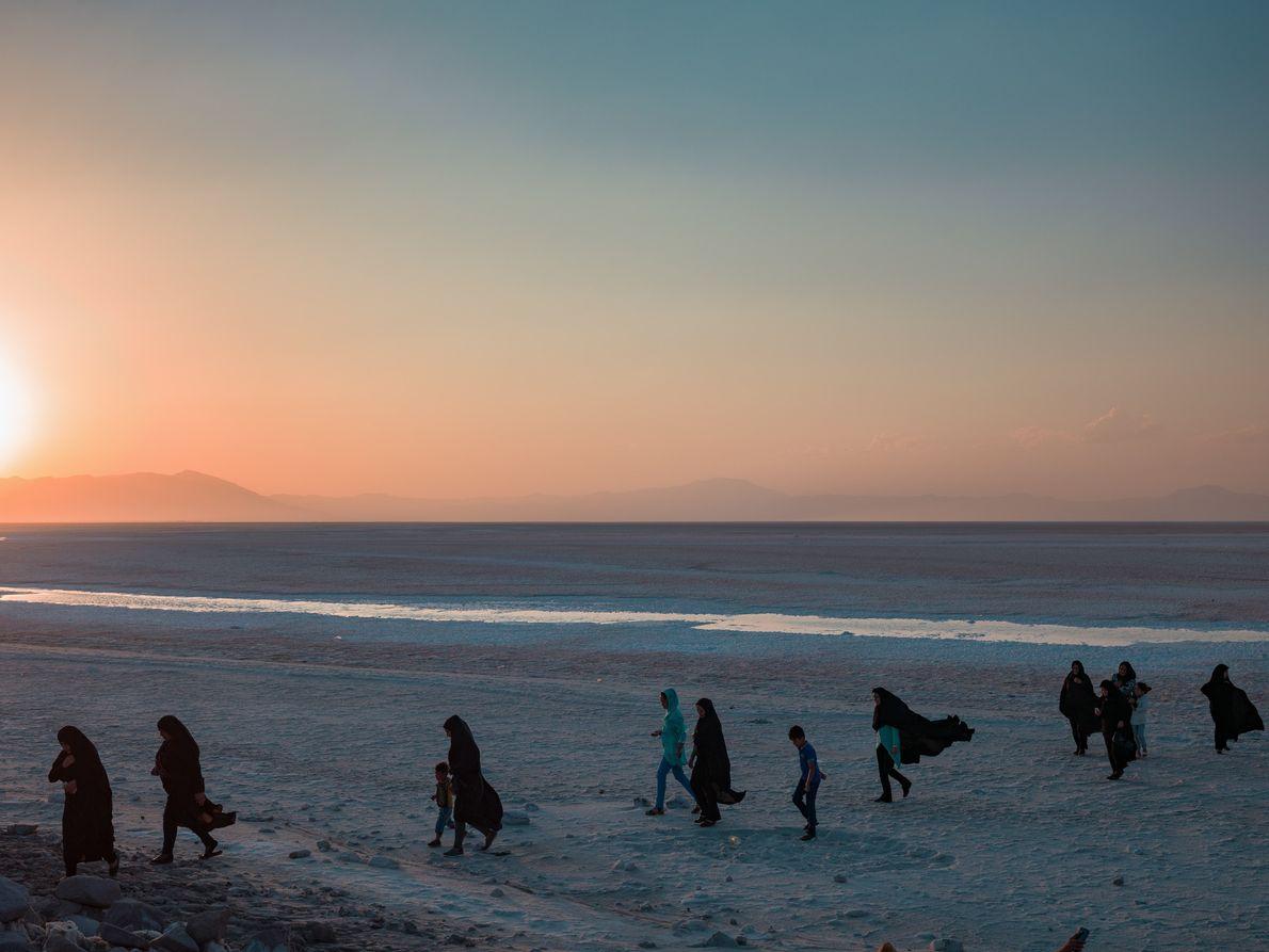 A family walks as the sun sets at Lake Urmia.