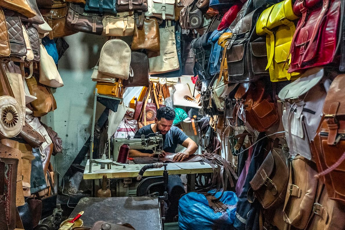 An artisan assembling a leather bag in his workshop. It requires experience and remarkable crafting skills. ...