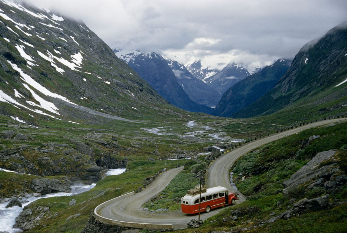 A bus negotiates a switchback road in a mountain-ringed valley.