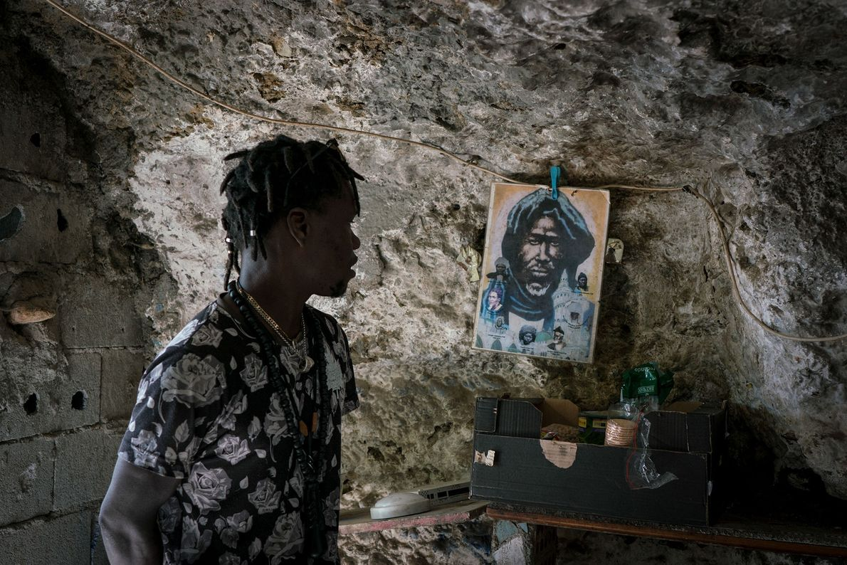 Malik, a Senegalese immigrant, looks at an image he's hung on the wall of his cave ...