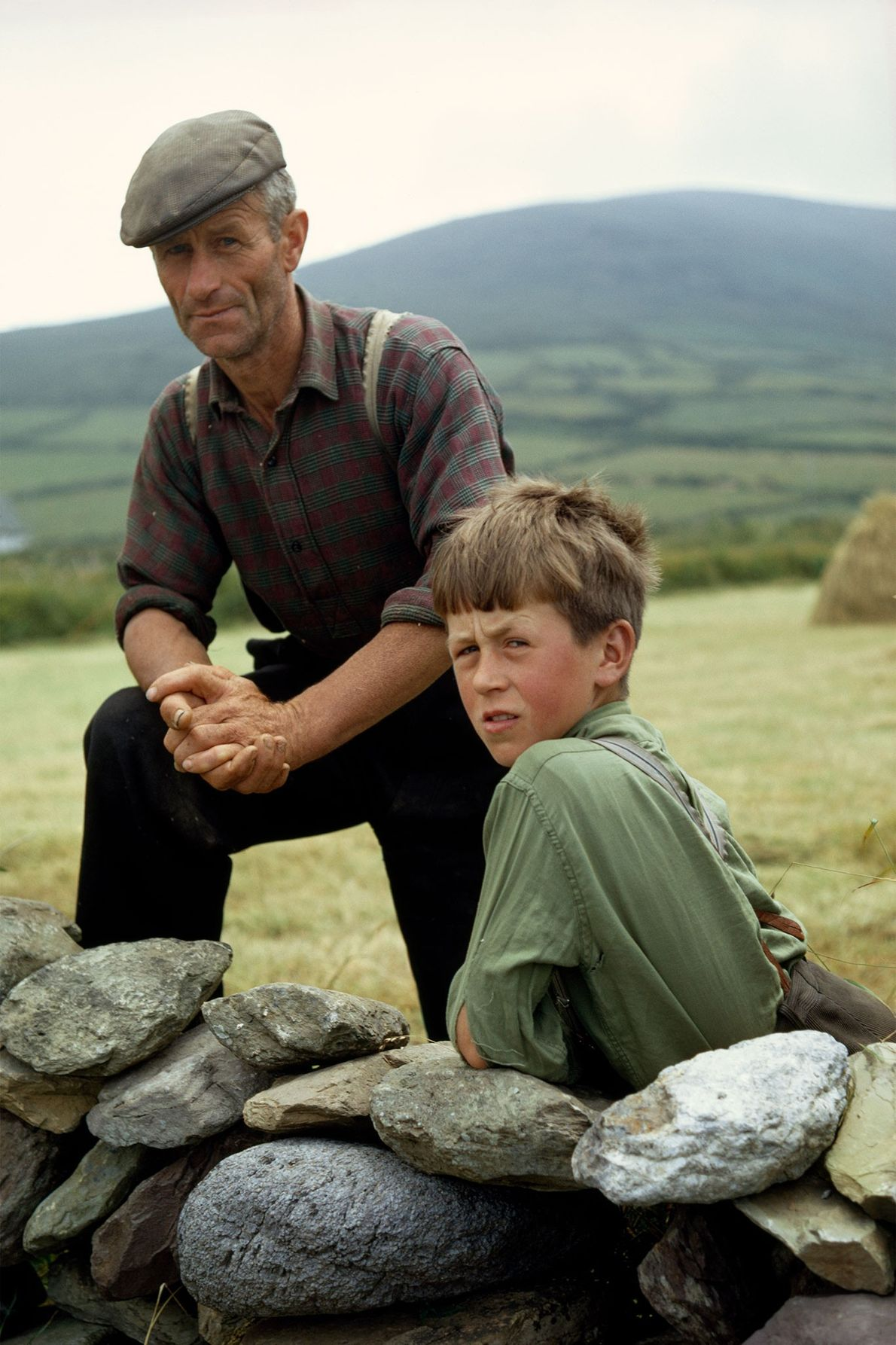 An Irish father-and-son farmer duo pause near a stone wall for a portrait on the Dingle ...