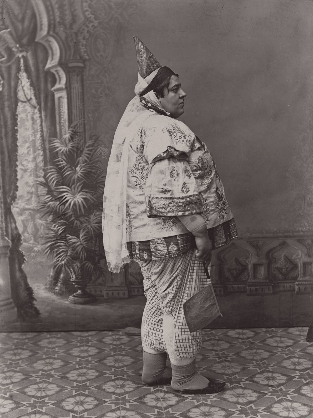 A woman clothed in satin and silk stands in a courtyard in Tunisia. Her pointed hat ...