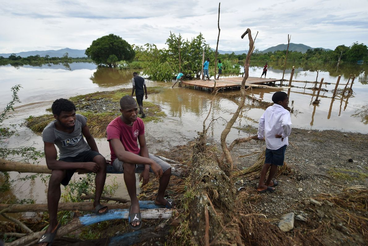 People sit on a tree next to a flooded river in Haiti on September 8.