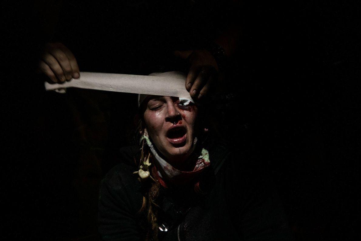 A protester is given first aid in a department store parking lot after she was struck ...