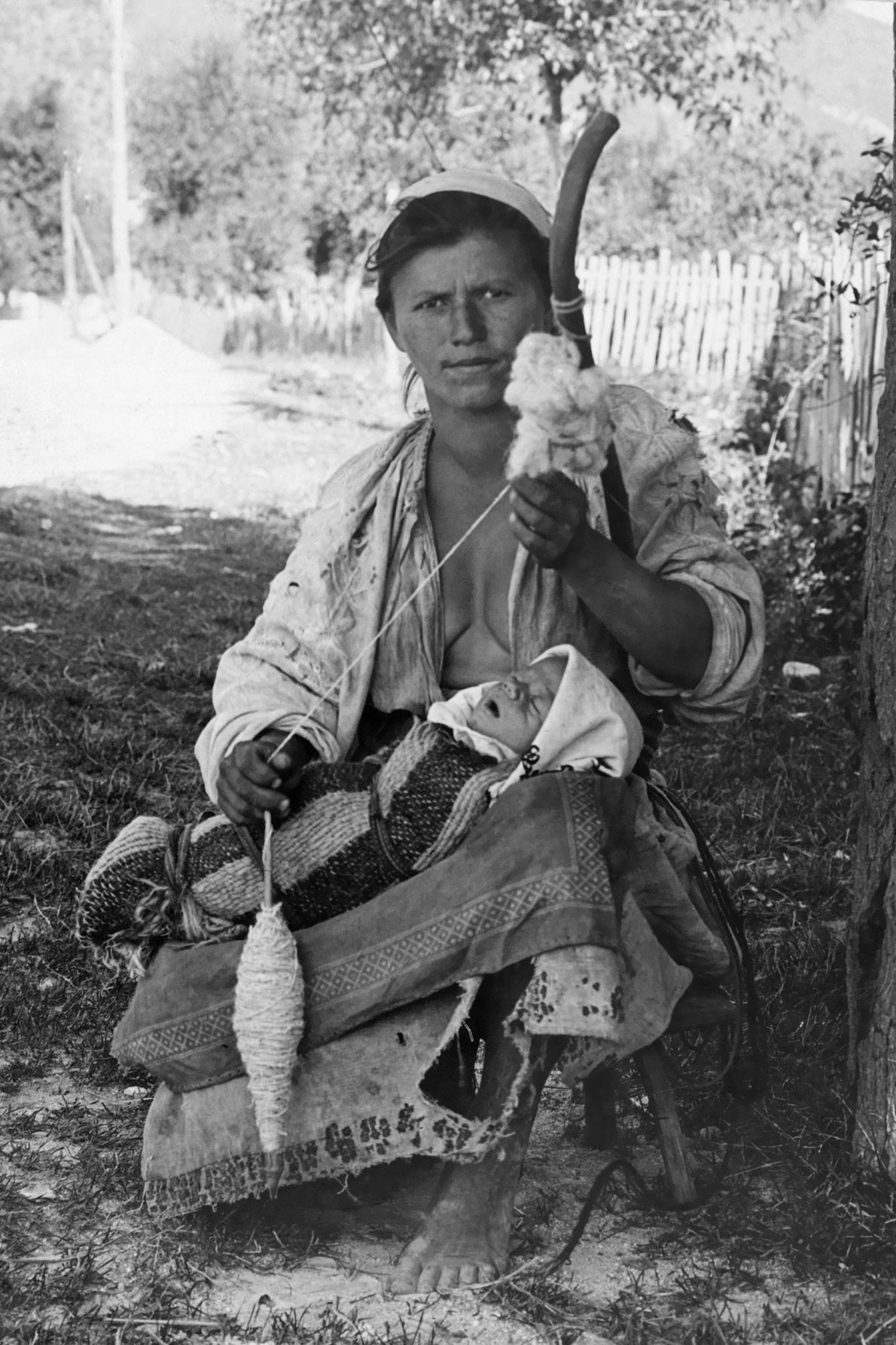 A Hungarian woman spins wool as her baby sleeps on her lap.