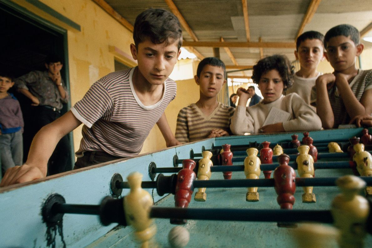 Refugee children play table football, also known as foosball or table soccer, at a camp in ...
