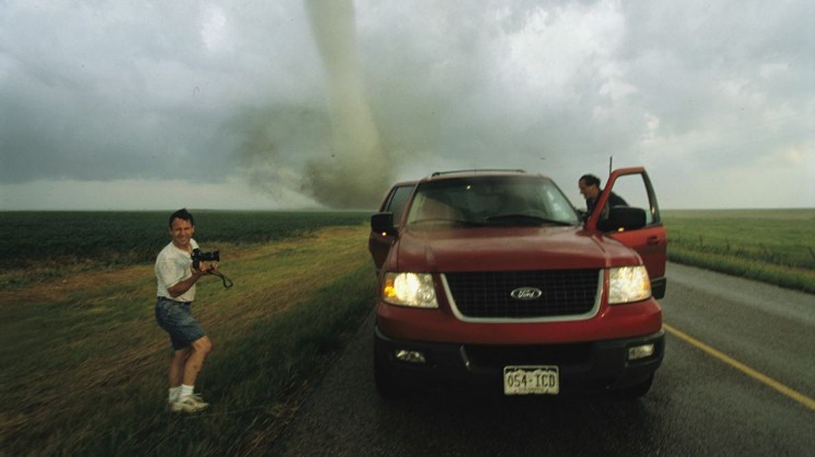 One tornado chaser with a camera poses while his partner gets into their truck as a ...