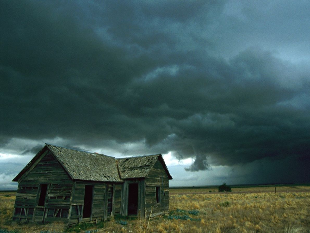 Heavy clouds hang low over a dilapidated homestead in the Midwest, foretelling a possible tornado. Tornadoes ...