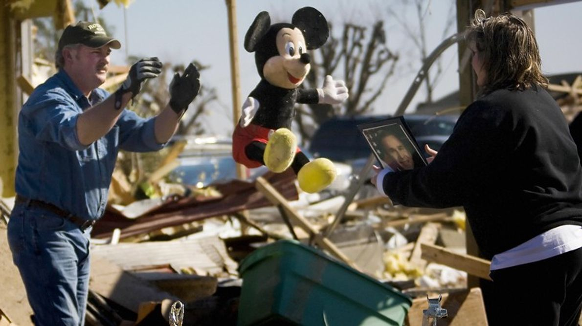 A man throws a stuffed animal to his wife as they clean up the debris from ...