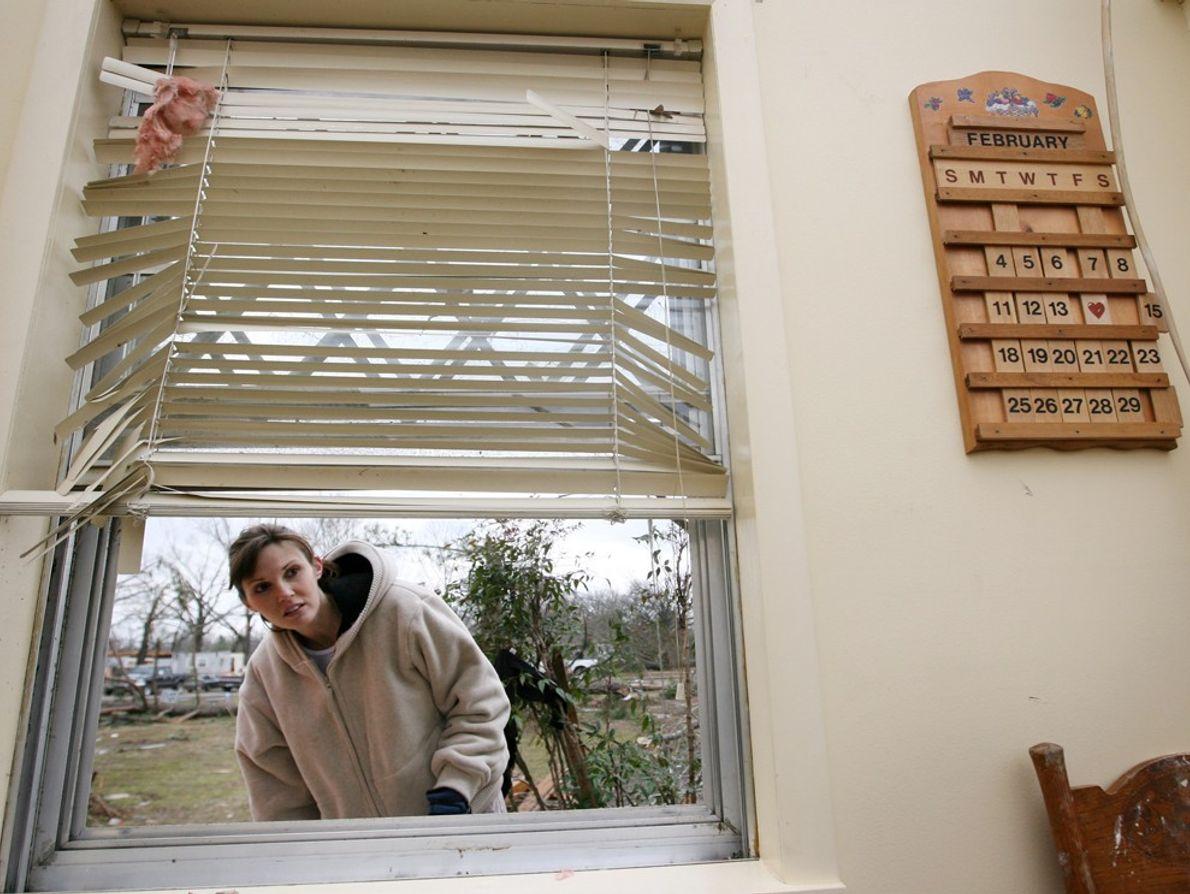 A woman looks through a broken window of a friend's house after a tornado over Atkins, ...