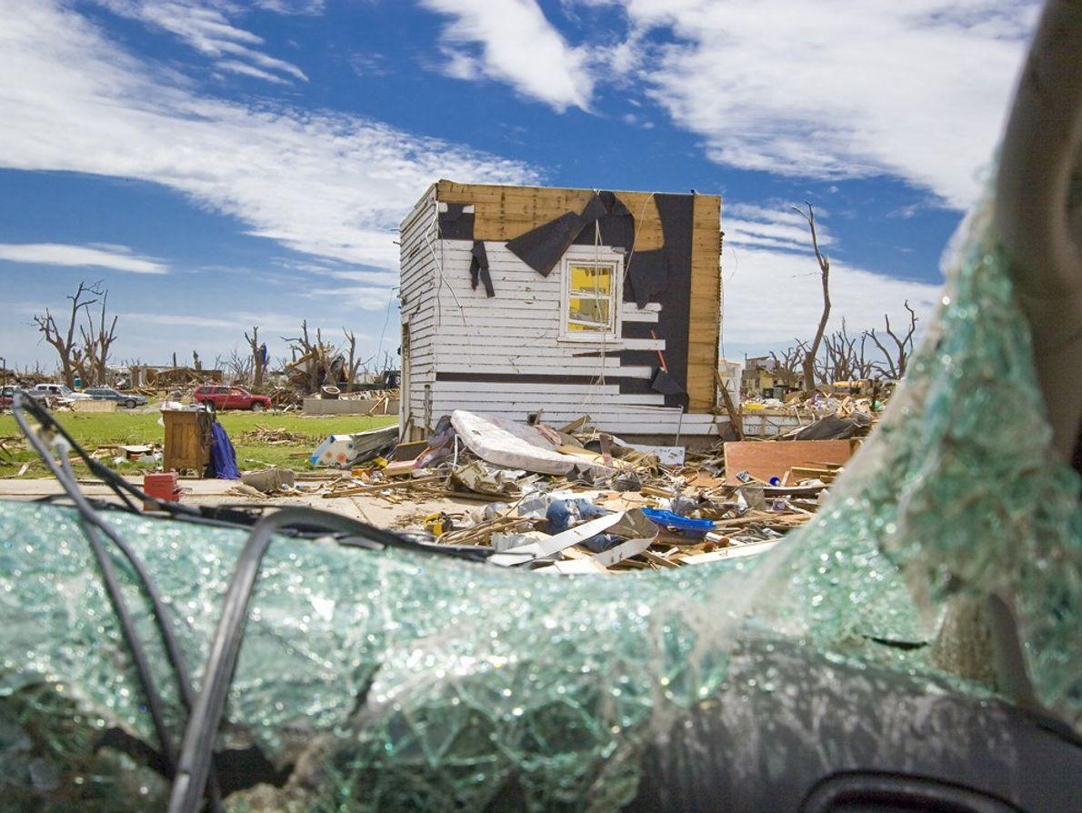 A broken safety glass window frames a destroyed house after an EF5 tornado struck Greensburg, Kansas.