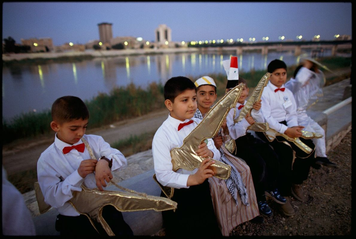 Picture of Iraqi schoolboys in white shirts and red bowties, carrying pretend gold automatic rifles