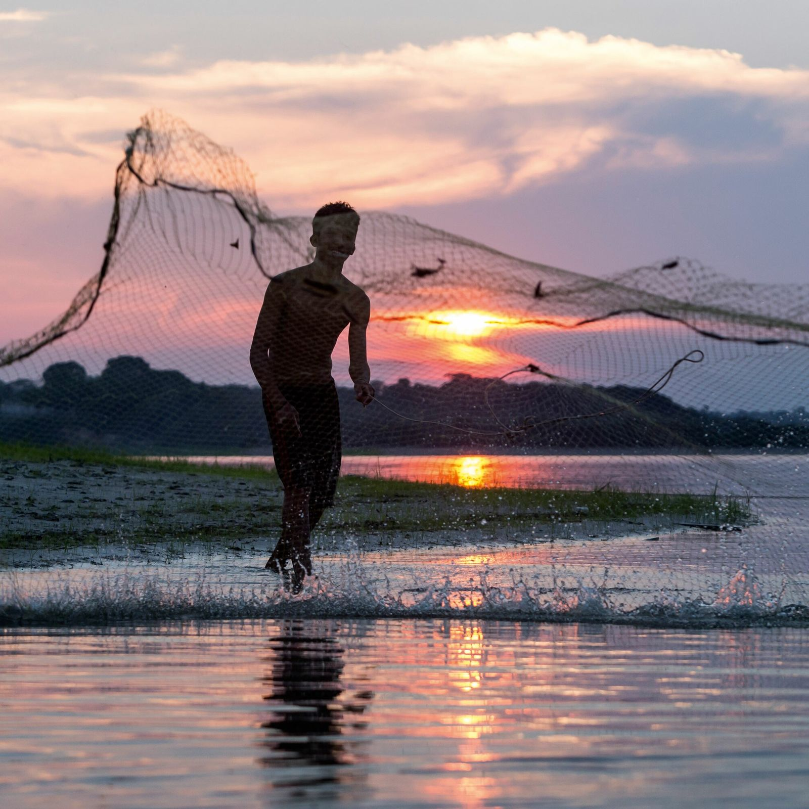 A fisherman casts his net into the Rio Negro, Brazil.