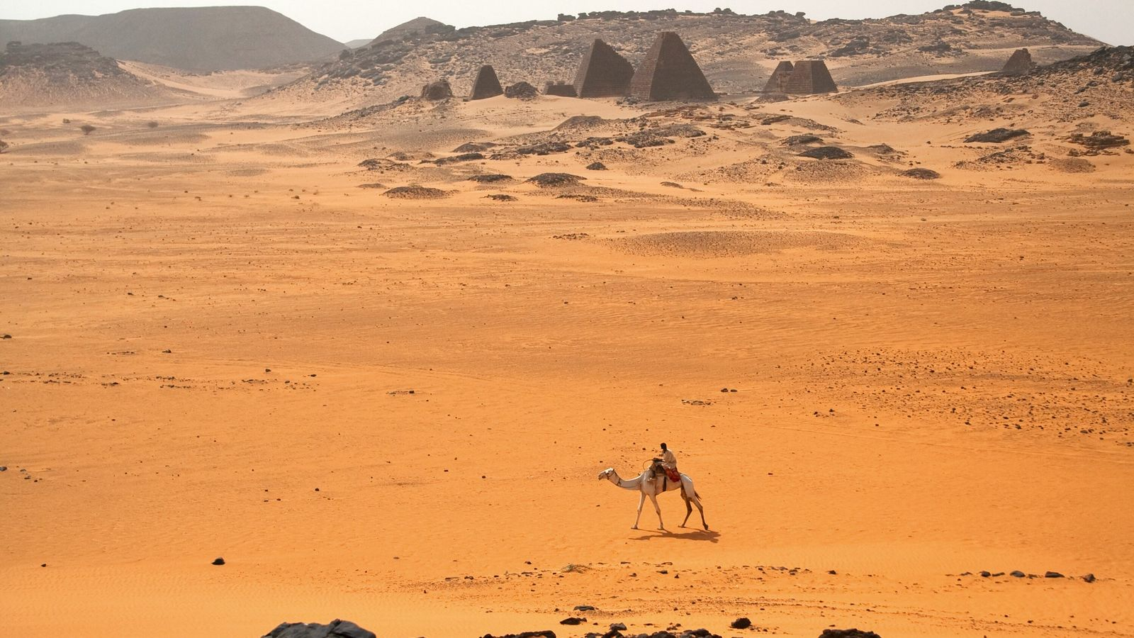 A camel and rider pass the pyramids of Meroë, Sudan.