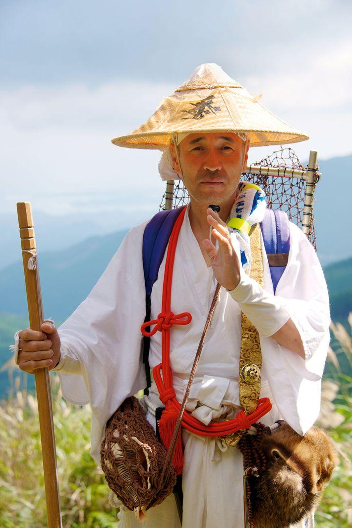 A Shugendo Yamabushi monk dressed in traditional suzukaki robes walks the Kumano Kodo path.