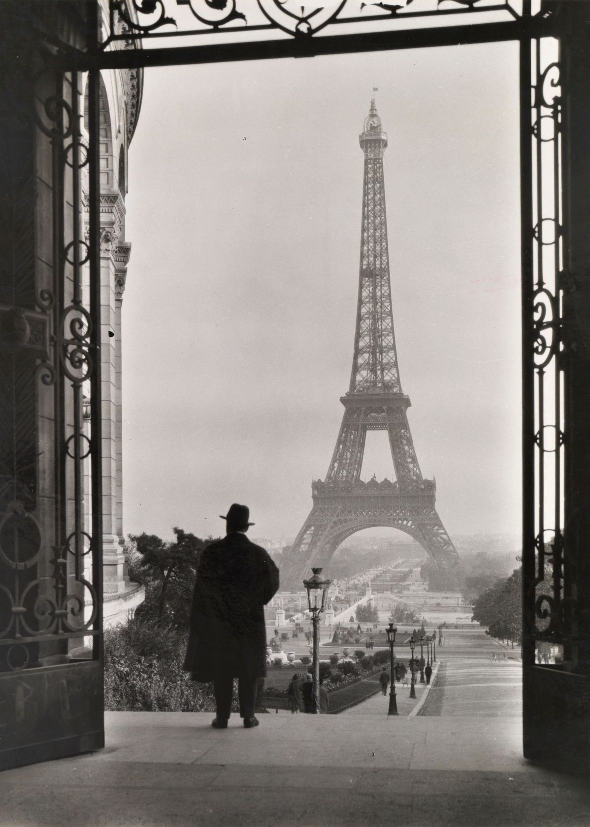 Forty years after completion of the Eiffel Tower, a man soaks in the iconic view.