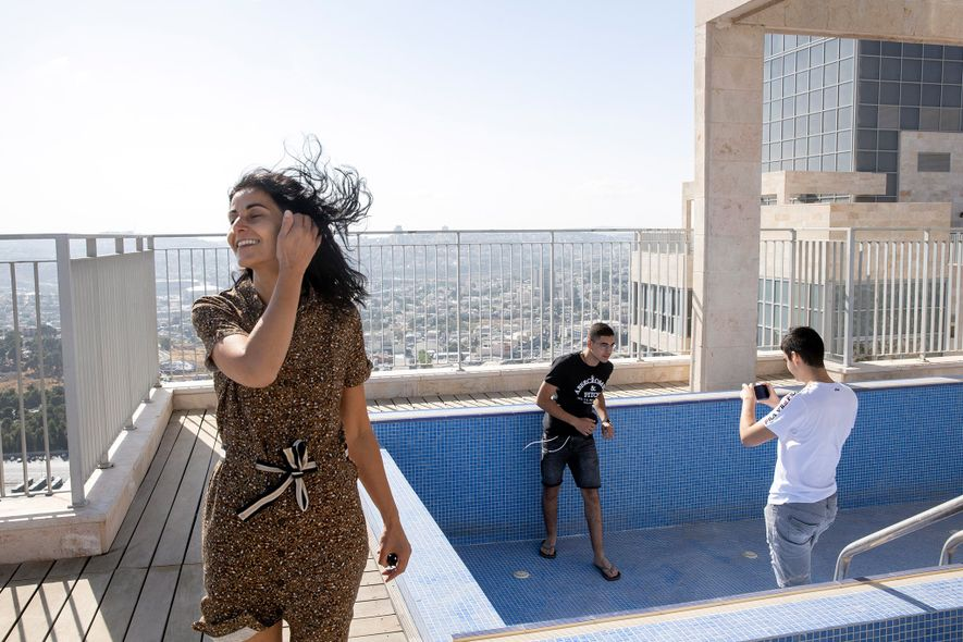 On their first day in Jerusalem, Yael, Gabriel, and Netanel Zeitoun explore the rooftop of their ...
