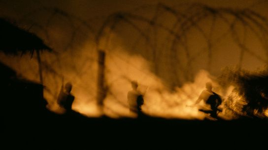 A flaming inferno flushes Viet Cong soldiers from a hut at night in the Mekong Delta ...