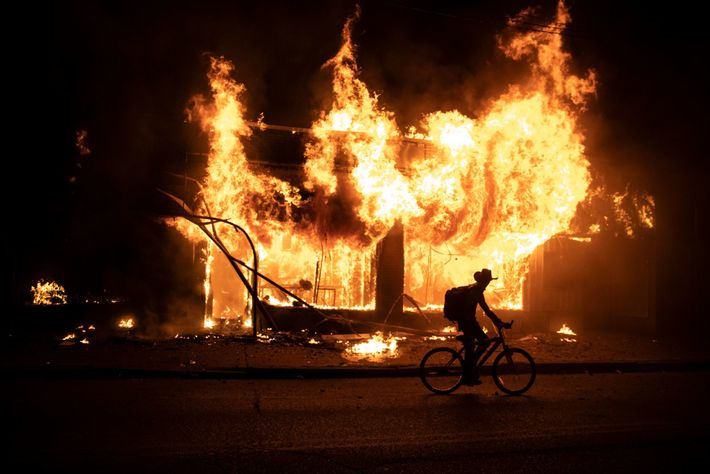 A protester bikes past a building set ablaze during ongoing demonstrations over the death of George ...