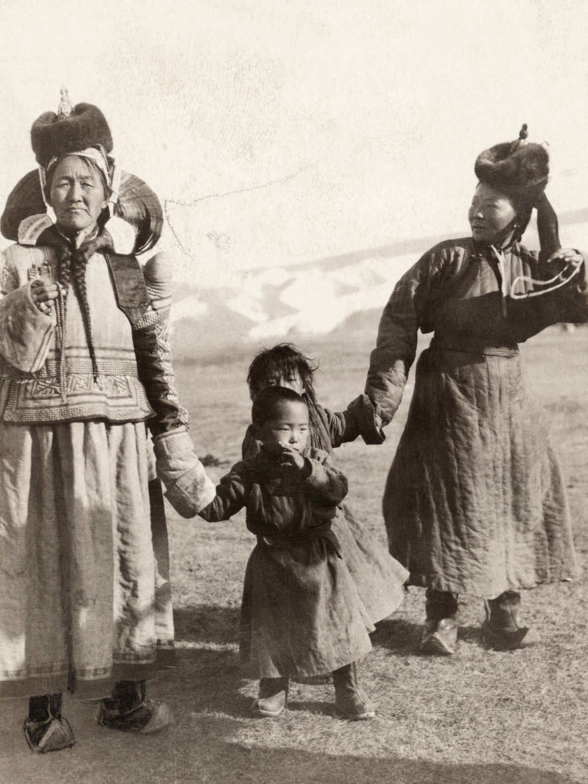 Women walk hand in hand with their children in northern Mongolia.