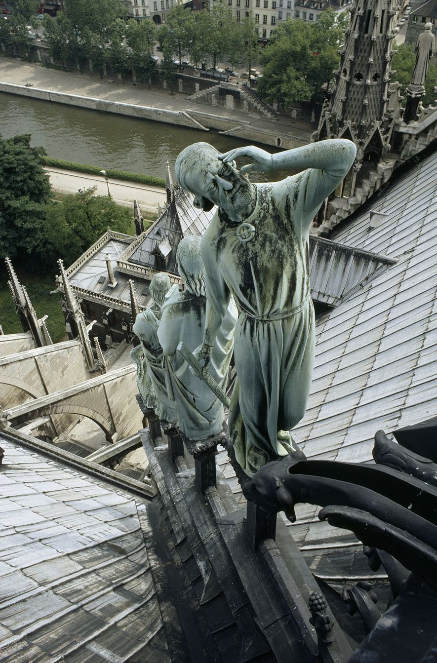 Rank of copper saints stands below the central spire of Notre Dame, all but one gazing ...