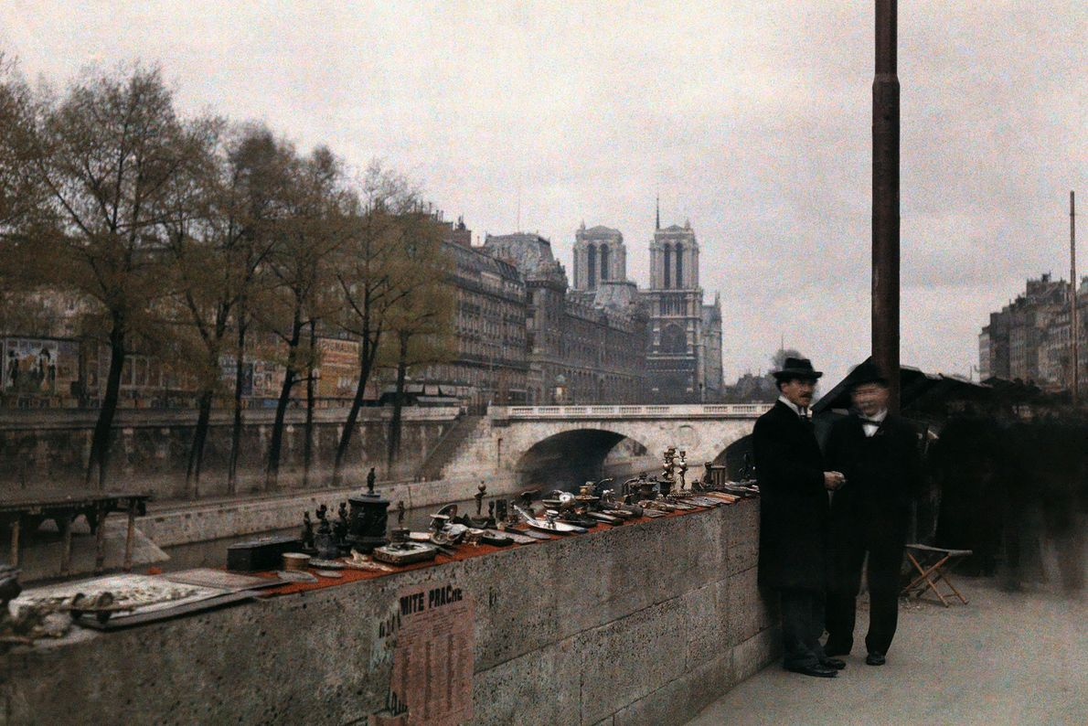 Two men stand next to trinkets for sale on the banks of the Seine in the ...