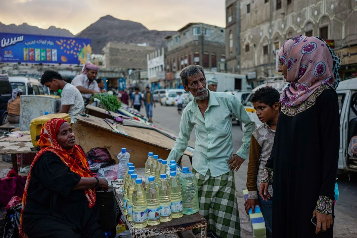 A woman sells plastic bottles of gasoline— unaffordable and inaccessible to millions across Yemen — in ...