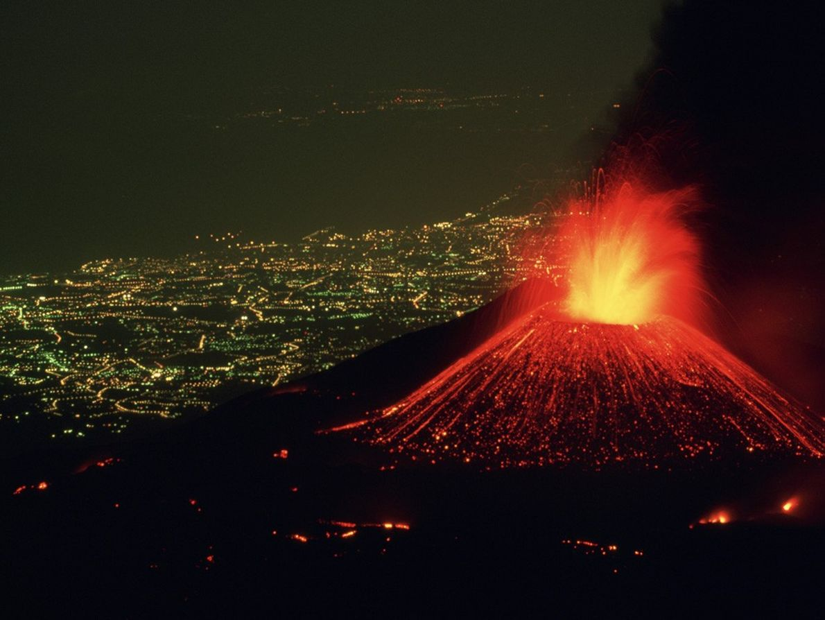 Perched  above the lighted city of Catania, Italy, Mount Etna hurls a fountain of  ...