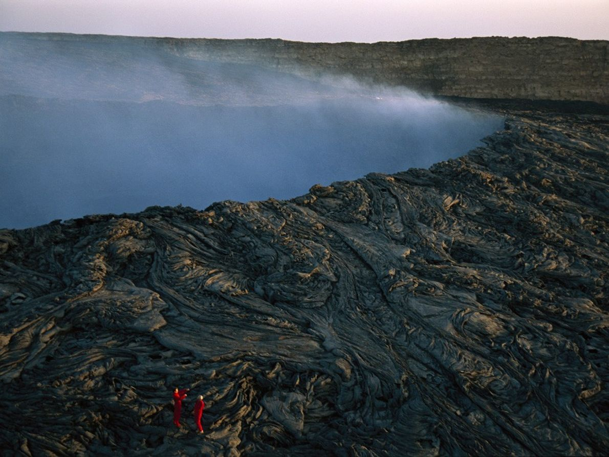 Climbers mount whorls of lava on the caldera of Ethiopia's Ertale Volcano as steam escapes from ...