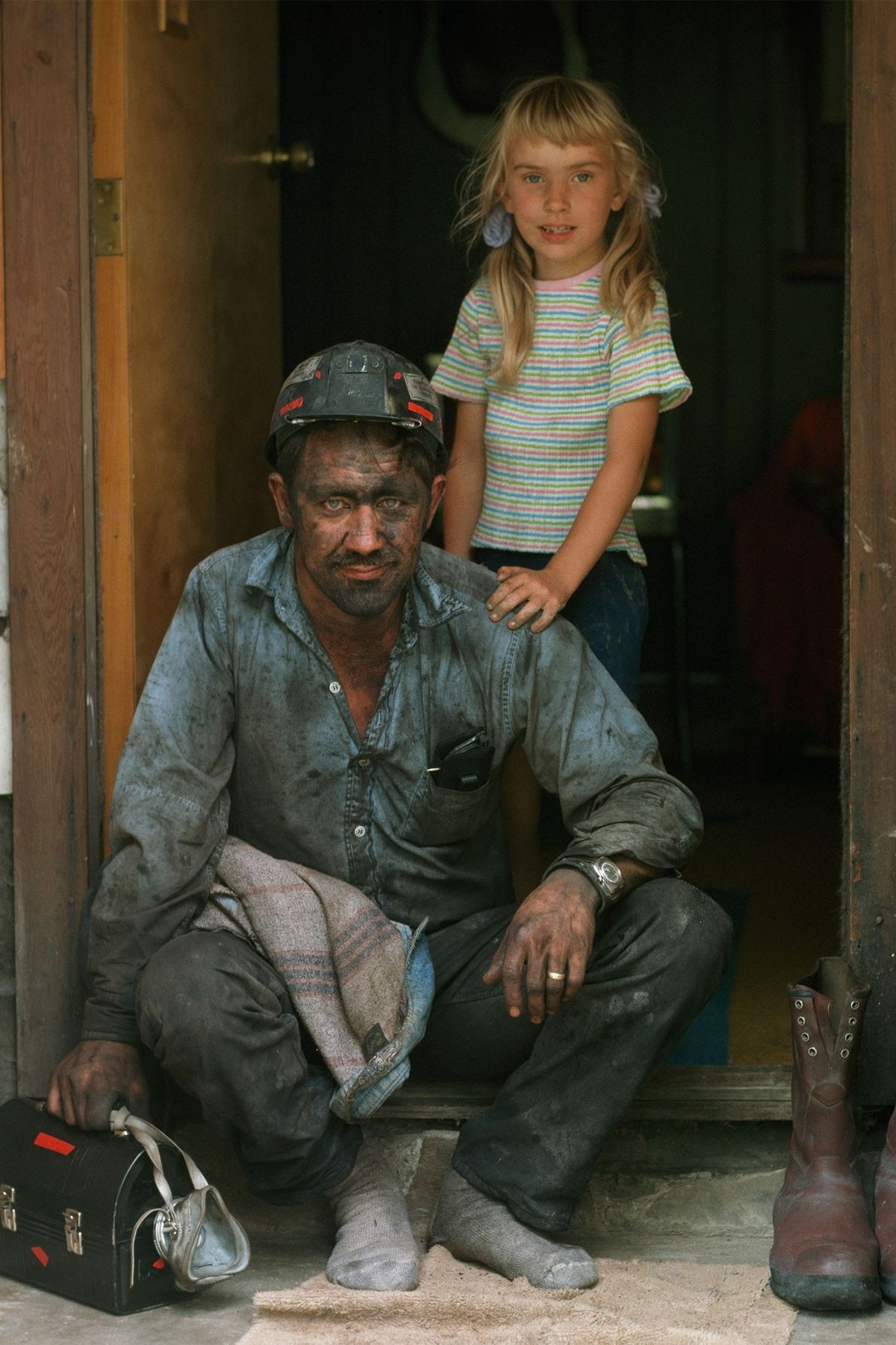 A miner sits on a stoop as his daughter rests her hand on his shoulder in ...