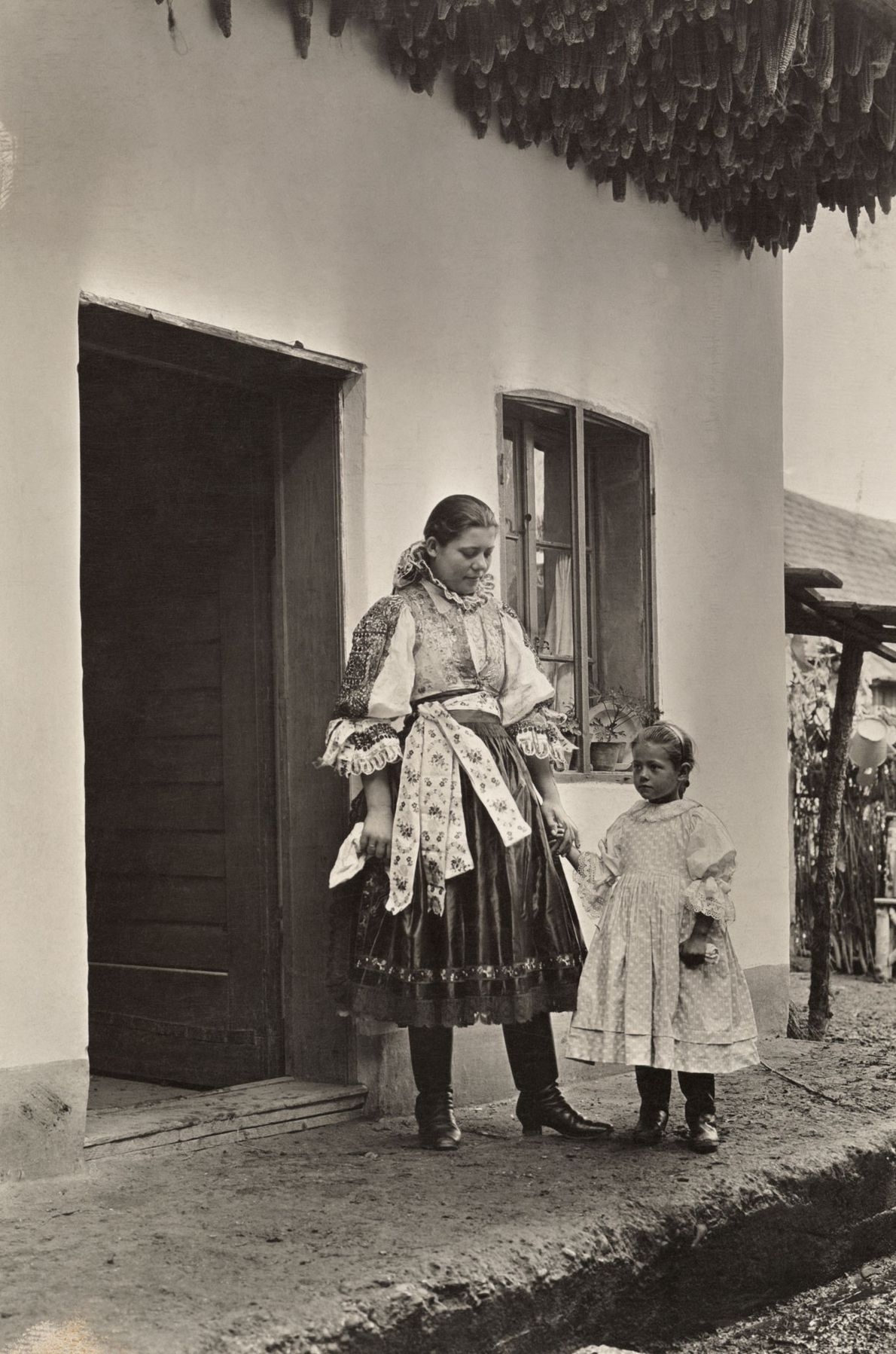 A mother and child stand under corn hung to dry over the entrance to their home ...