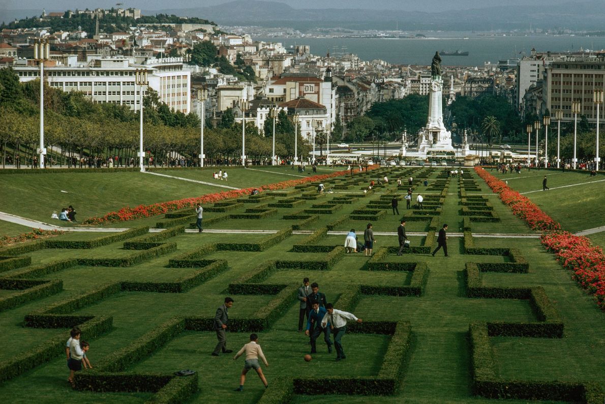 People stroll through a sculpted garden in Lisbon, Portugal, while a group of boys play a ...