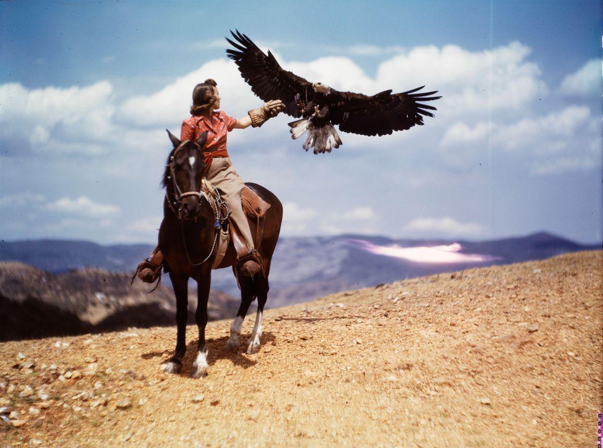 A woman on horseback calls out to a bald eagle.
