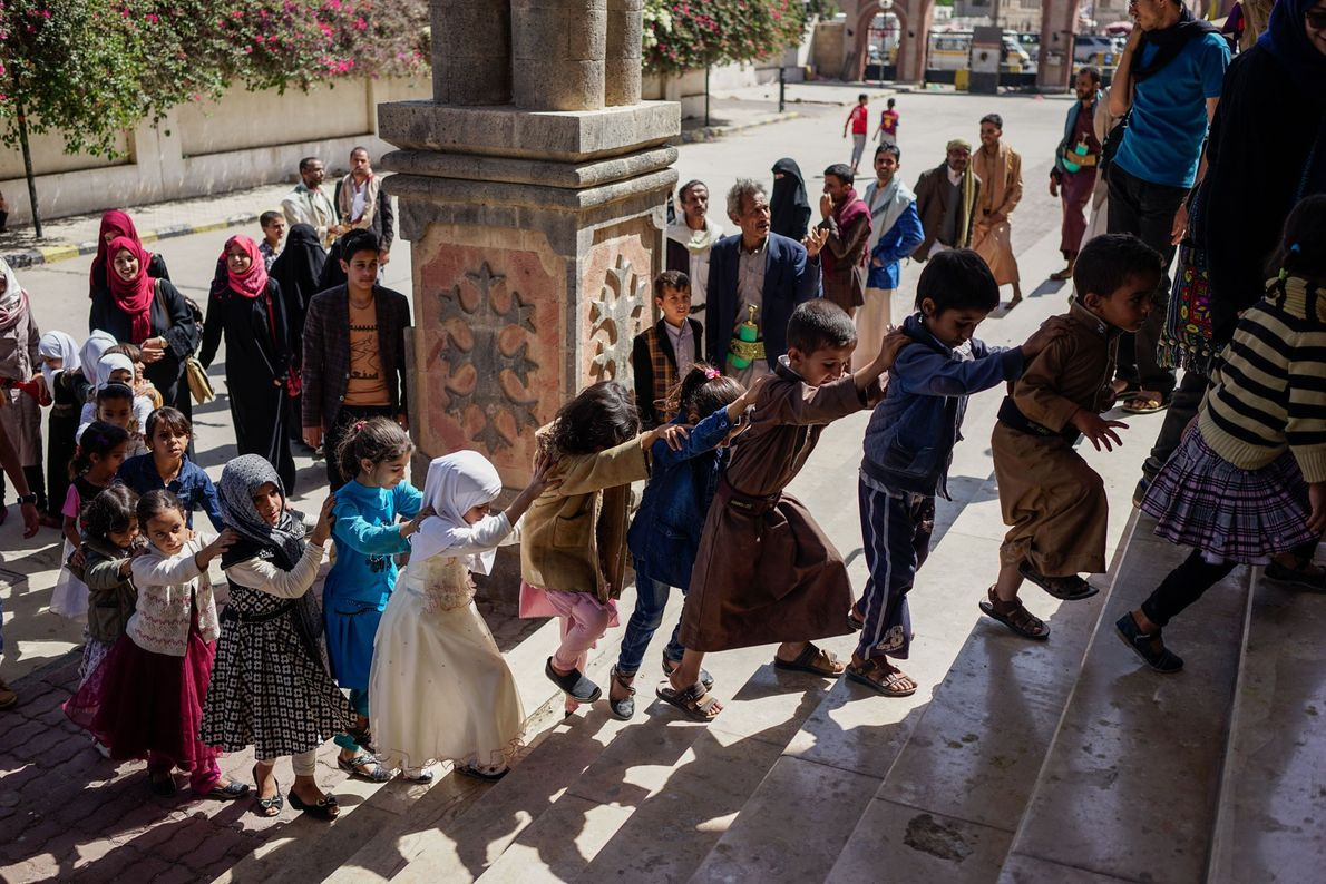 Parents and their children deliver symbolic offerings of pocket change to a post office in Sana'a, ...