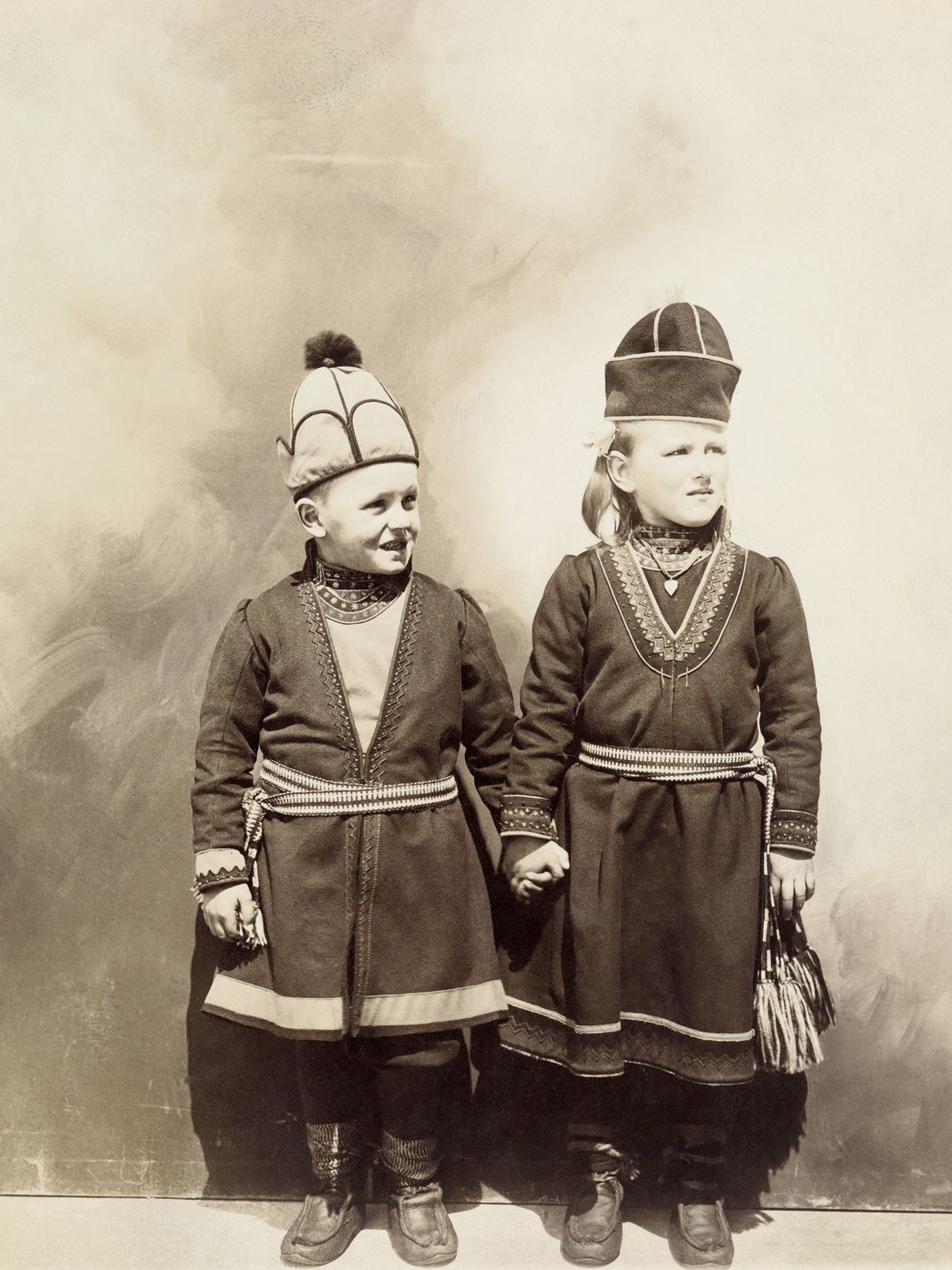 Two Norwegian children who immigrated to the U.S. in the early 1900s hold hands while wearing ...
