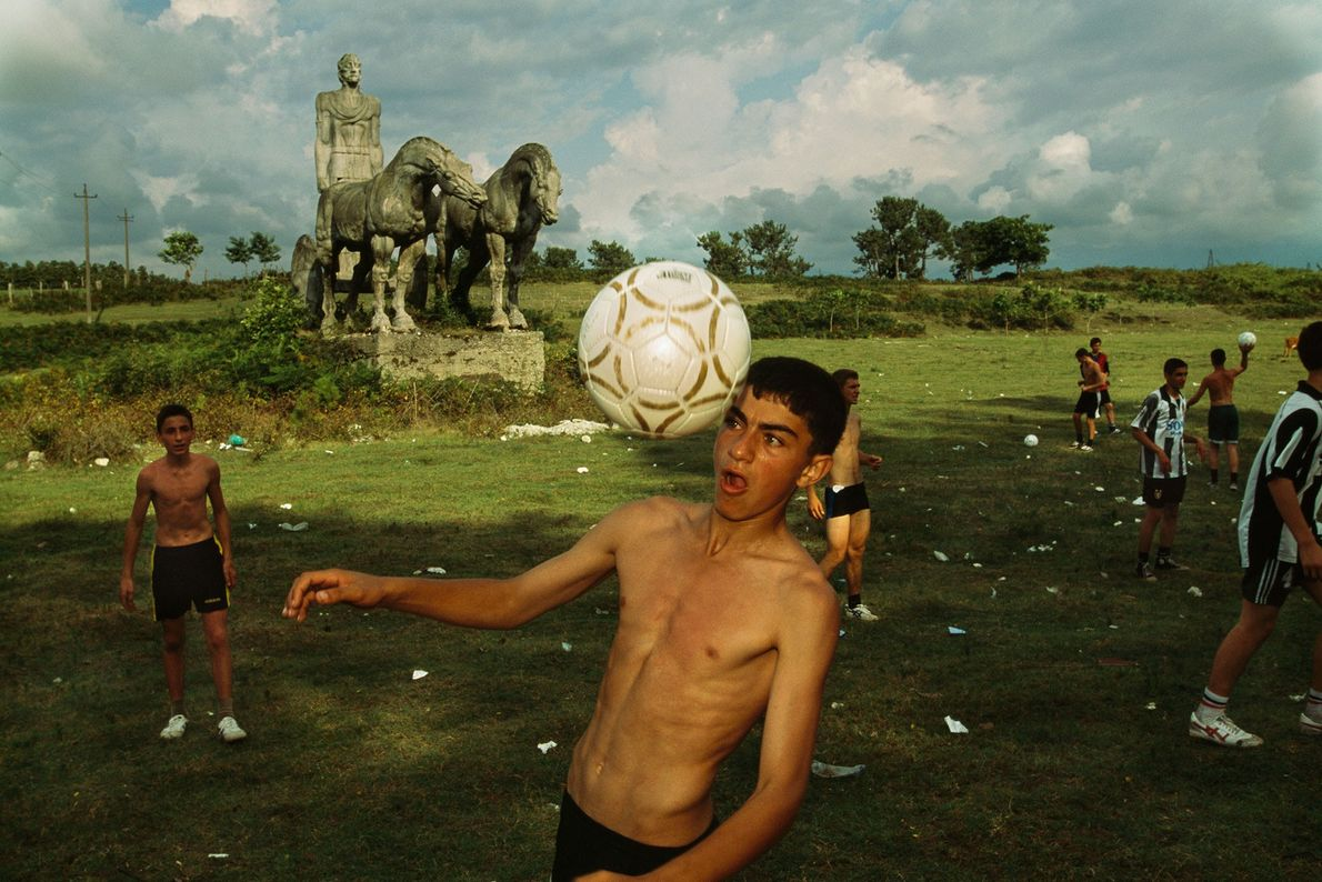 A boy bounces a football off his head while playing on a field.