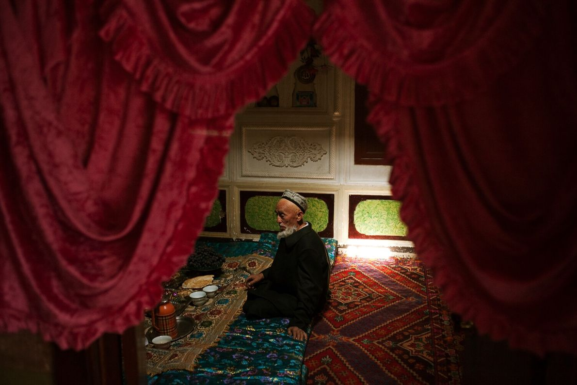 Picture of an elderly man seated on intricate rugs in Kashgar, Xinjiang, China, preparing to take ...