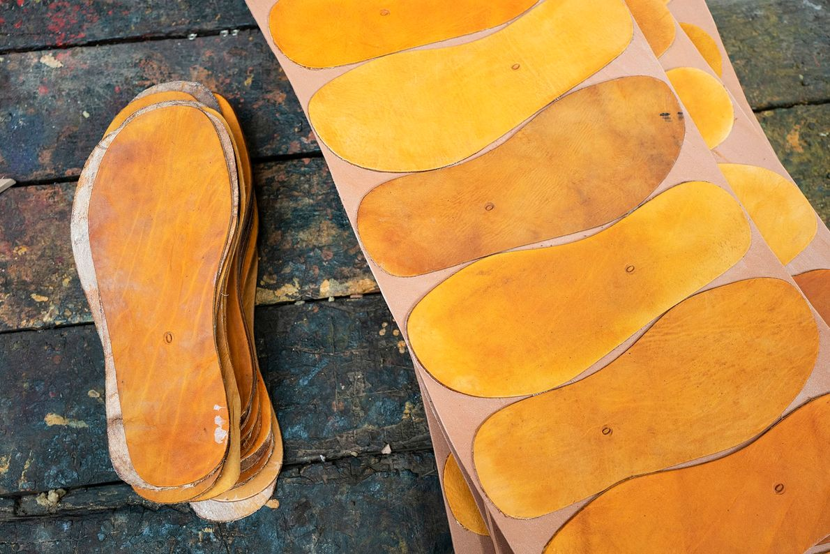 Inner soles are drawn on the hide using a cardboard template, according to the model being ...